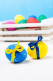 Set of colorful Easter eggs in a white wooden box on blue backgrounds. Yellow and blue egg wrapped with tape Stock Images