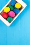 Set of colorful Easter eggs in a white wooden box on blue wooden backgrounds. With decorative flowers Stock Image