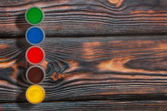 Set of colorful finger paint jars on a rustic background Stock Image