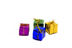 Set of colorful gifts on white background. Christmas gift box in foliage wrap with gold thread bow. Royalty Free Stock Image