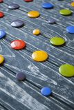 A set of colorful glass buttons for clothes. On a dark wooden background Royalty Free Stock Image