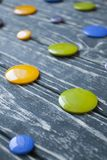 A set of colorful glass buttons for clothes. On a dark wooden background Royalty Free Stock Photography