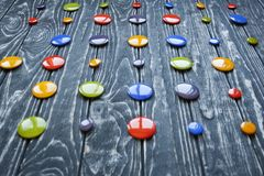 A set of colorful glass buttons for clothes. On a dark wooden background Stock Images