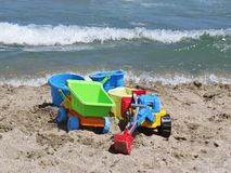 Set of Colorful Kid Child Toys Laying on Sandy Beach with Waves in Background royalty free stock image