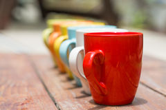 Set of colorful mug cups on a old wooden table Stock Images