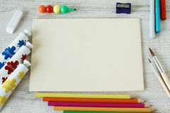 Set of colorful paints, crayons and brushes with blank album. Paper on wooden background with scattered materials for drawing around it Stock Image