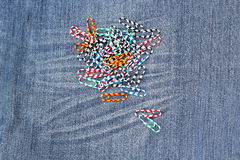 Set of colorful paperclips on a jeans background Stock Photo