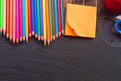 Set of colorful pencils on black board. Border of colorful pencils with with oprange sticker on black board Royalty Free Stock Photo