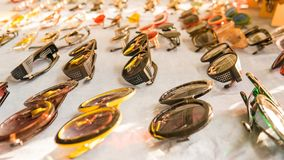 Set of colorful sunglasses for sale in a store. Different sunglasses on light coloured background. Summer eyeglasses.Fashion collection stock images