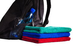 Set of colorful towels and backpack with bottle of water. Isolated on white background Stock Photos