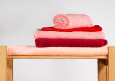 Set of colorful towels on wooden shelf,  on white backgr Royalty Free Stock Photography