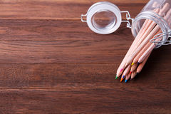 Set of coloured pencils in a glass pot on a wooden table Stock Photo