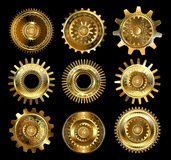 Set of complex gears. Set of vintage, patterned brass and gold gears on a black background Stock Images