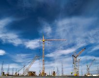 Set of construction cranes in building site. Construction cranes and machinery in project site building houses at blue sky background Stock Image