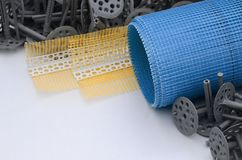 A set of construction items for the insulation of walls. Plastic dowels, a roll of mesh for the insulation of facades and a corner. Profile with a grid lie on royalty free stock photos