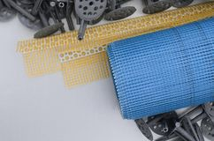 A set of construction items for the insulation of walls. Plastic dowels, a roll of mesh for the insulation of facades and a corner. Profile with a grid lie on stock photography