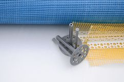 A set of construction items for the insulation of walls. Plastic dowels, a roll of mesh for the insulation of facades and a corner. Profile with a grid lie on royalty free stock photography