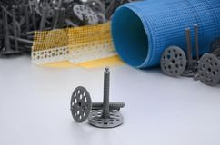 A set of construction items for the insulation of walls. Plastic dowels, a roll of mesh for the insulation of facades and a corner. Profile with a grid lie on stock photo