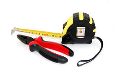 Set of construction tools. On white - tape measure and pliers Royalty Free Stock Image