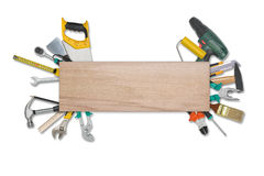 Set of construction tools  behind wooden plankisolated on a white background. Saw, glasses, tape measure, wrench Stock Images
