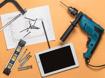 Set of construction tools to repair and white tablet on orange-brown table: drill, hammer, pliers, self-tapping screws. Roulette, level, drawing, pencil. Top Royalty Free Stock Photography