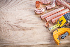Set of copper water pipe cutter connectors tape line on wooden b Royalty Free Stock Images