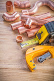 Set of copper water pipe cutter fixtures tape line on wooden boa Royalty Free Stock Photo