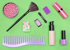 Set of cosmetic bag essentials. Foundation, blush, lipstick, eyeshadow, makeup brushes, perfume, nail polish, comb Stock Photos