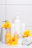 Set of cosmetic bottles with orange flowers over white tiled wal Royalty Free Stock Images