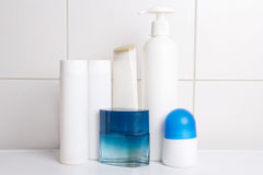 Set of cosmetic bottles over white tiled wall Royalty Free Stock Images