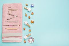 A set of cosmetic tools for manicure and pedicure on a blue background. Gel polishes, nail files and nippers and top view. Composition for a card with a place stock photo