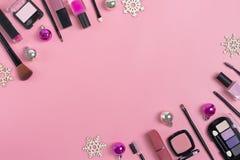 Set of cosmetics and accessories. Lipstick, perfume, eye shadow, mascara, ring, nail polish, eyelash forceps, blush, earrings on pink background Chriastmas royalty free stock image