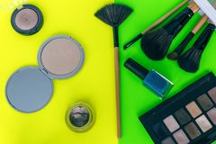Set cosmetics makeup, brush, eye shadow on yellow-green background royalty free stock image