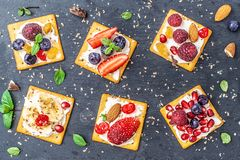 Set of crackers with various fruit close-up on black stone plate.  stock photography