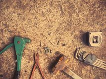 Set of craftsman tools and screws. On dirty concrete floor, vintage filter effect Stock Photos