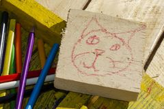 Set for creativity. Wooden box with pencils. Sketches of cat drawings. Drawing a cat on a blackboard and colored pencils and crayons in a wooden box stock images