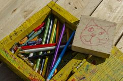 Set for creativity. Wooden box with pencils. Sketches of cat drawings. Drawing a cat on a blackboard and colored pencils and crayons in a wooden box royalty free stock photography