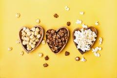 Set cukierki i solony popkorn w drewnianych pucharach zdjęcia stock