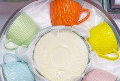 Set of cups of different colors with saucers.  stock photography