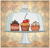 Set of cute cakes under glass dome. Stock Photos
