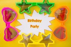 Set of cute celebratory sunglasses saying happy birthday.Birthday party concept. Funny sunny glasses on yellow royalty free stock image