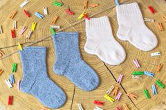 Set of cute knitted cashmere newborn baby socks hanged on pins against wooden background royalty free stock photography