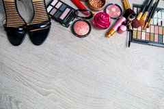 Set of decorative cosmetics and brushes near black heeled sandals on grey wooden background. Various makeup products Royalty Free Stock Photography