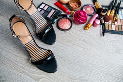 Set of decorative cosmetics and brushes near black heeled sandals on grey wooden background. Various makeup products Royalty Free Stock Photos