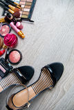 Set of decorative cosmetics and brushes near black heeled sandals on grey wooden background. Various makeup products Royalty Free Stock Photo