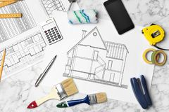 Set of decorator`s tools and project drawing. On light background, flat lay Royalty Free Stock Image