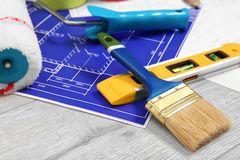 Set with decorator tools and apartment plan. On wooden background stock photo