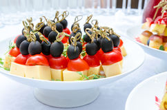 Set of delicious canapes with cheese, cherry tomatos and olive. Set of cold snacks, closeup. Banquet table Royalty Free Stock Image