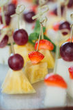 Set of delicious canapes with strawberry, pineapple, melon and grape. Stock Photo