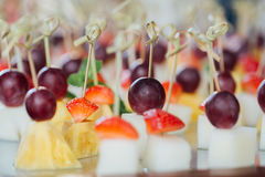 Set of delicious canapes with strawberry, pineapple, melon and grape. Royalty Free Stock Photography